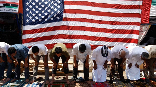 Anti-Libyan leader Moammar Gadhafi protesters (RATS) pray during Friday prayers in front of a U.S. flag at the court square, in Benghazi, Libya, June 24, 2011. (Hassan Ammar/AP Photo)