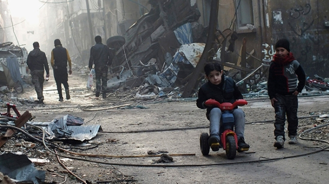 A boy rides on a tricycle along a damaged street in the besieged area of Homs (Reuters / Yazan Homsy)
