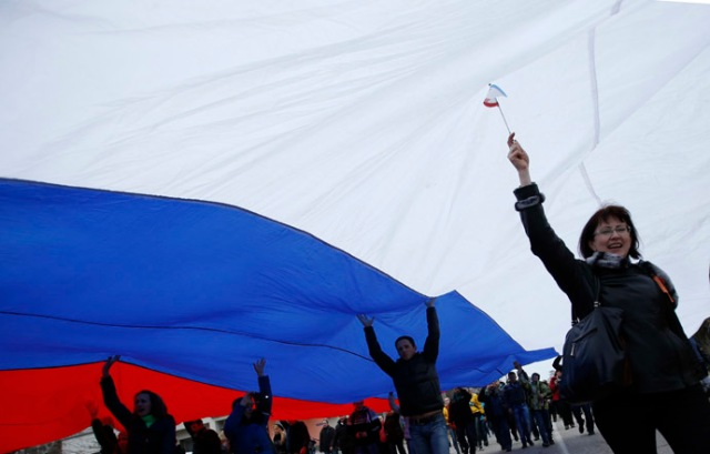 People march on the street with a giant Russian flag in Simferopol