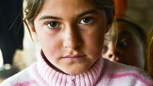 The file photo shows a displaced Izadi girl living in an unfinished building outside the town of Dohuk, in Iraq's Kuridistan region.